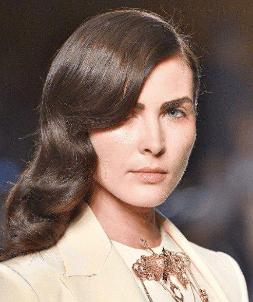 Coiffures de fête : Femme avec des boucles de style vintage sur des cheveux bruns de longueur moyenne aux épaules sur un podium.