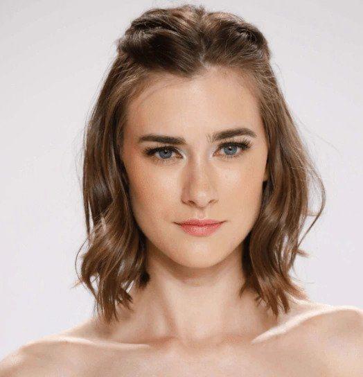 Coiffures de fête : Femme aux cheveux bruns à la longueur des épaules avec des ondulations douces épinglées en arrière au sommet.