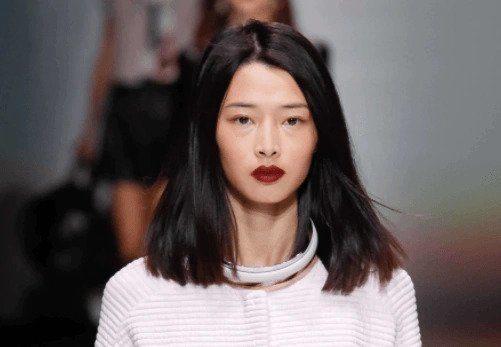 Coiffures de fête : Femme en défilé avec des cheveux droits brun foncé à la longueur des épaules et des lèvres en forme de baie.