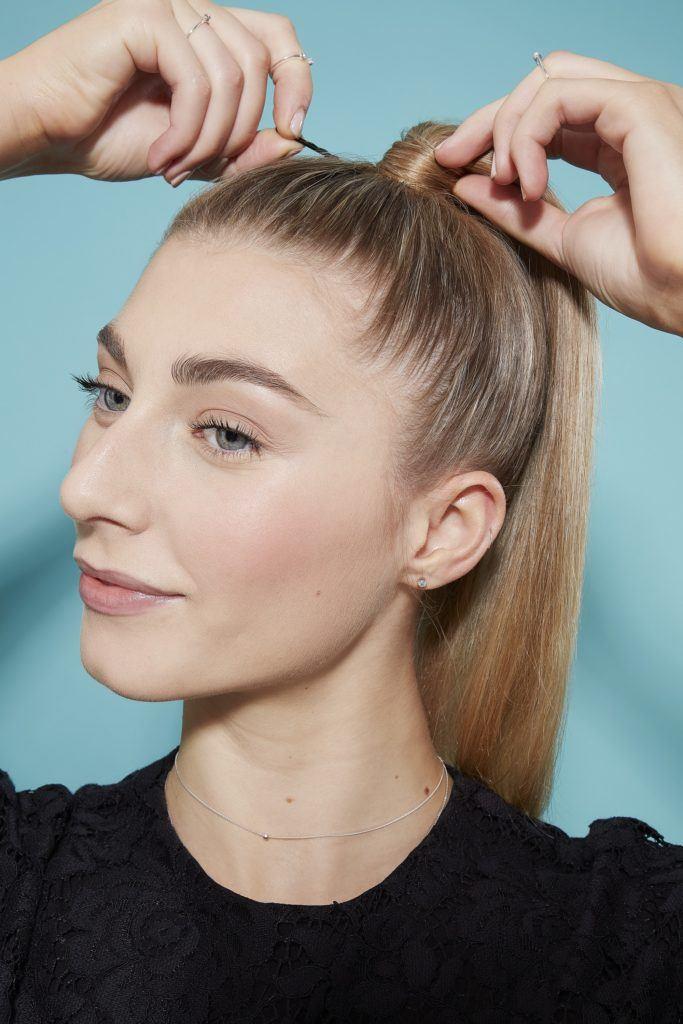 Une femme blonde crée une haute coiffure en queue de cheval