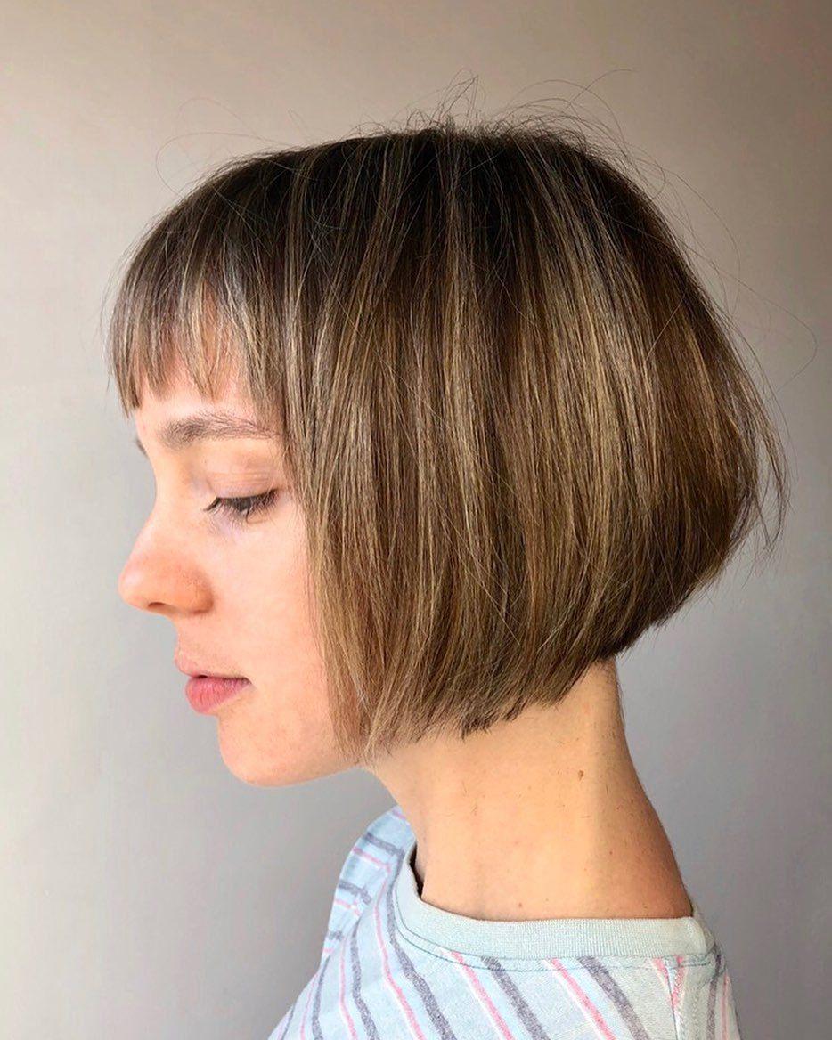 Femme à la bronde inversée avec une courte coiffure et une frange de cheveux