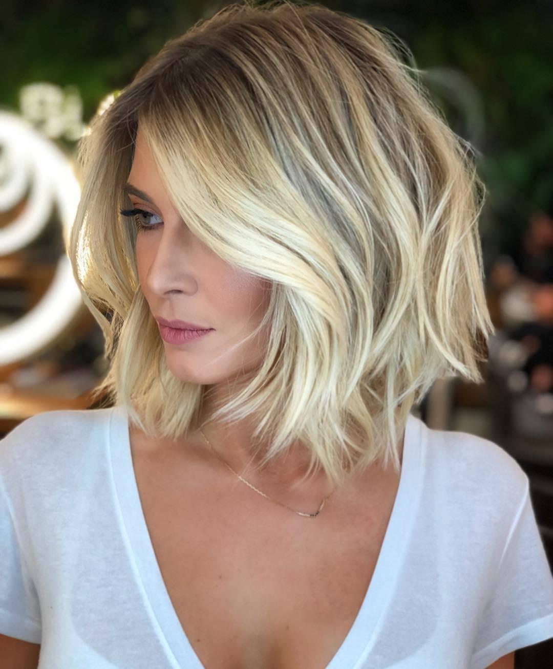 Femme au bob court d'une blonde éclatante avec une frange ondulée