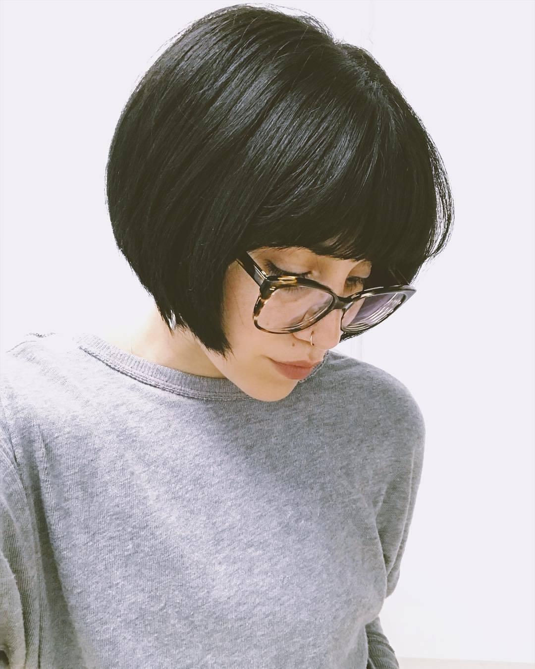 Femme avec un bob marron foncé super court et arrondi avec une frange épaisse
