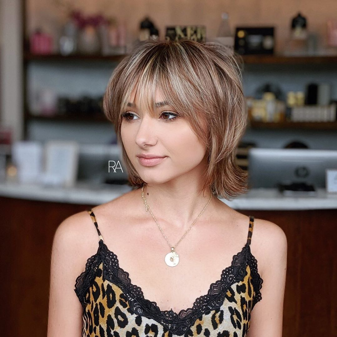 Femme avec un short moderne miel et un bob à poils bruns avec une frange hirsute