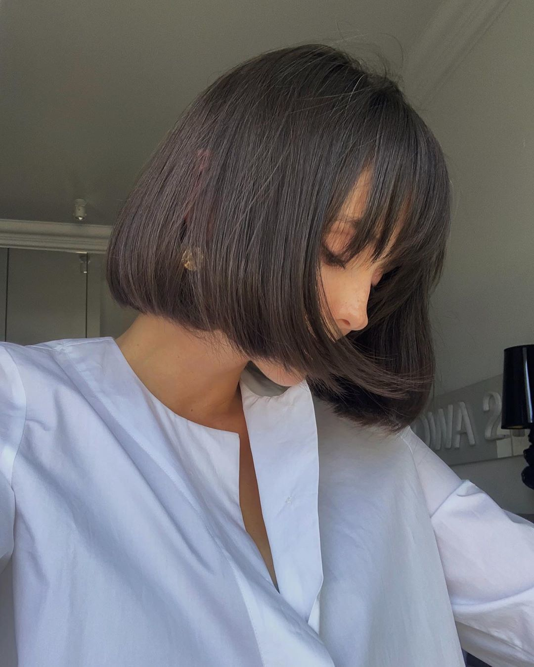 Femme au bob court enroulé avec une frange de cheveux