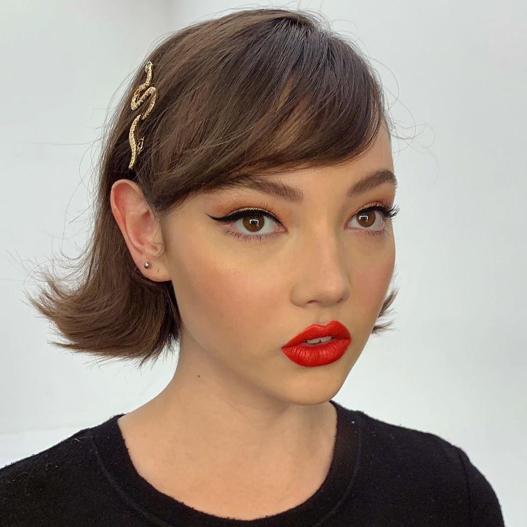 Femme au bob court marron d'inspiration vintage avec une frange de cheveux
