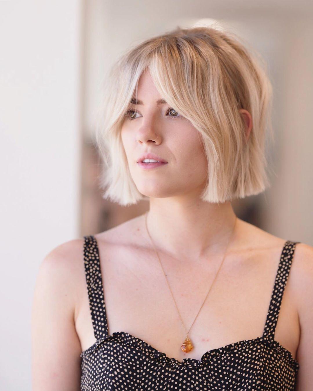 Femme avec un bob court blond naturel à la frange fendue