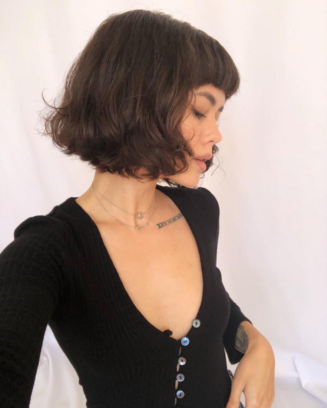 Femme avec un bob ondulé lâche avec une frange complète