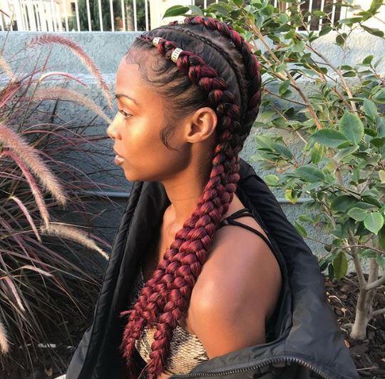 Femme aux tresses de maïs bordeaux avec poignets de cheveux