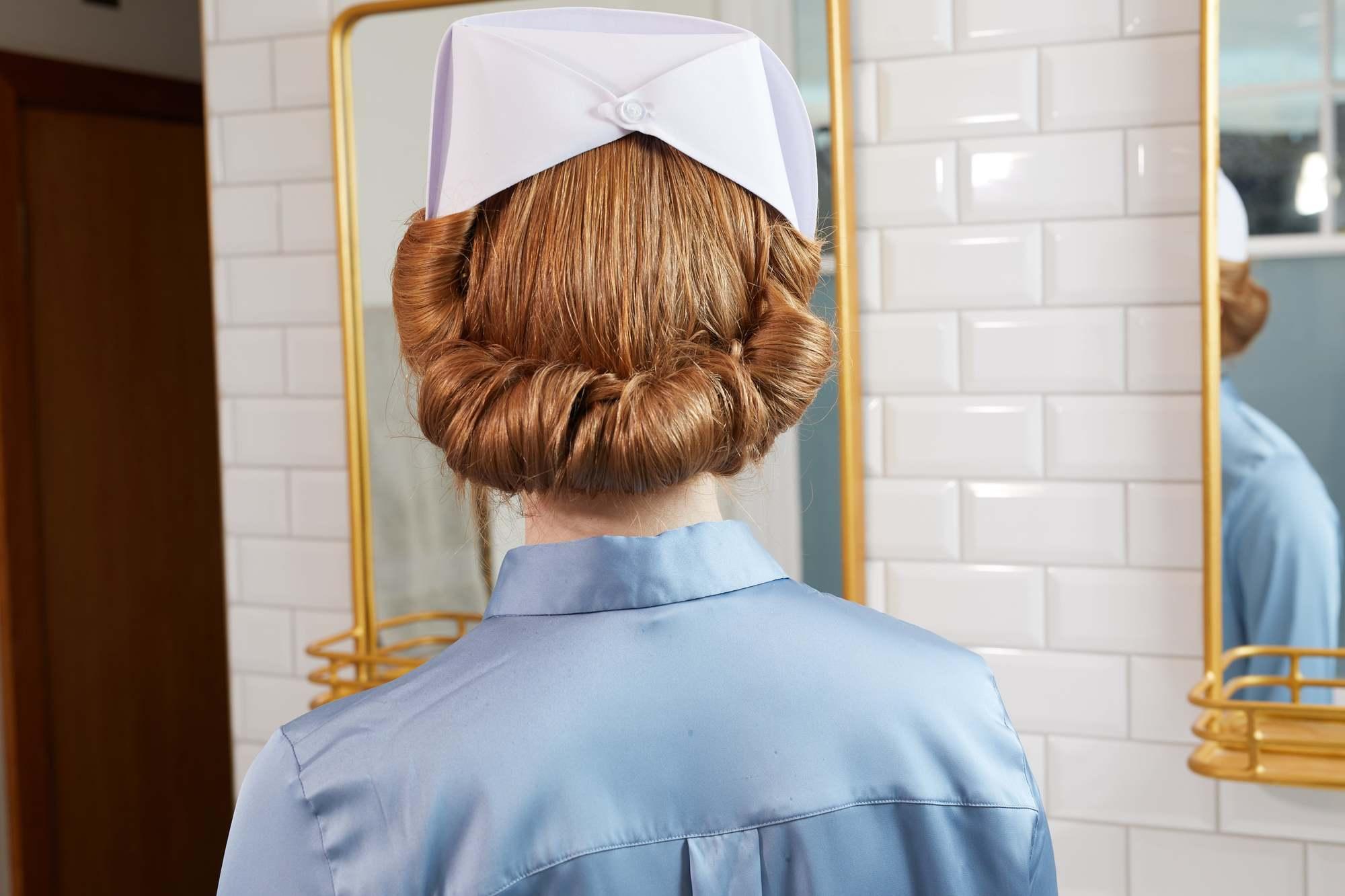 Une femme aux cheveux roux coiffée en infirmière inspirée de Ratched Updo