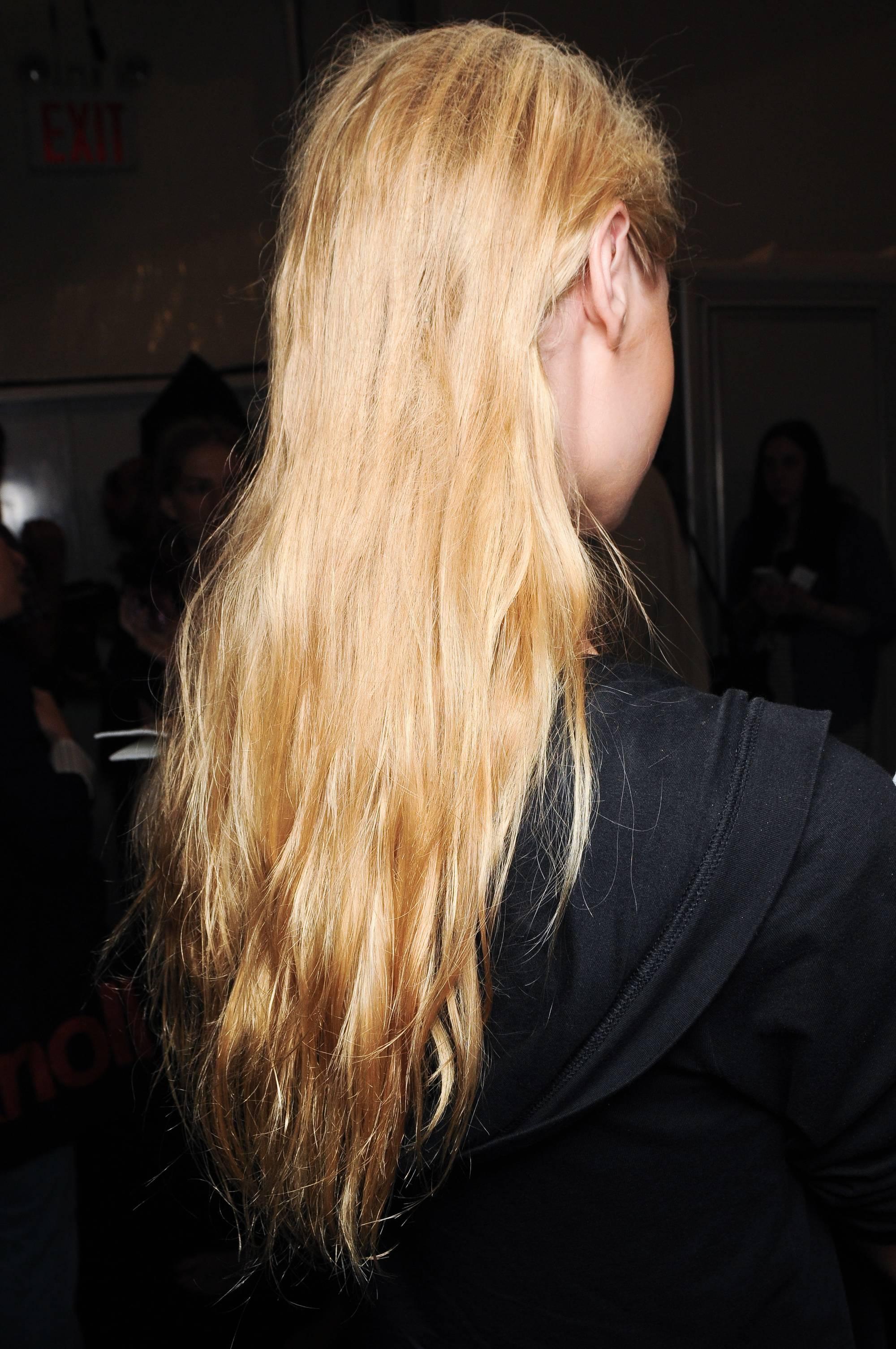 Cheveux cassants : Une fille blonde aux cheveux longs dans les coulisses du SS12 Vera Wang portant un haut noir.
