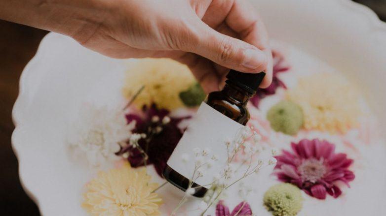Main tenant une bouteille marron devant un bol de fleurs