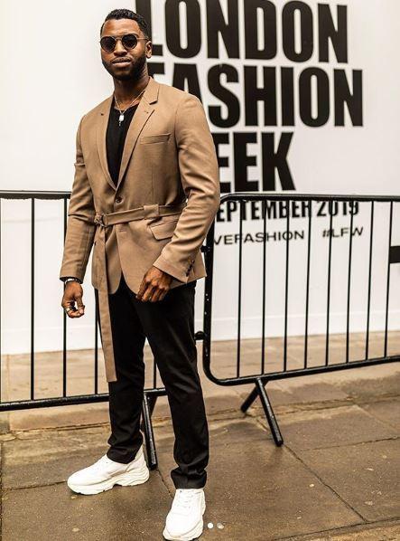 Homme barbu noir à la semaine de la mode de Londres portant une veste de couleur havane
