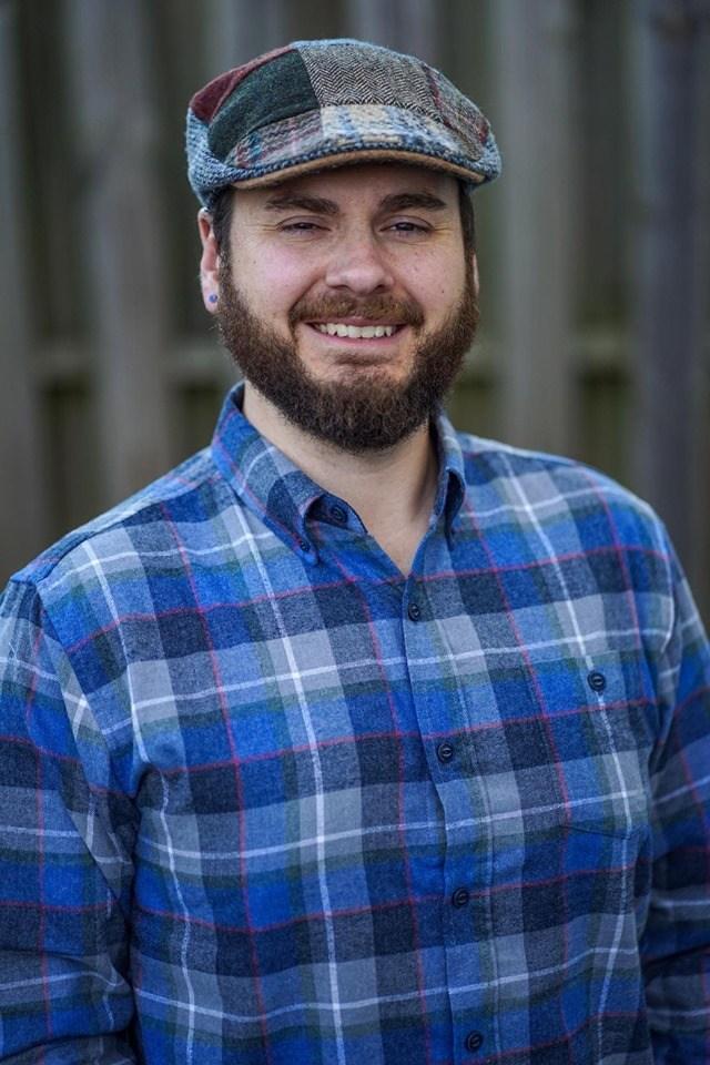 Image d'un homme avec un haut à carreaux et une barbe souriante