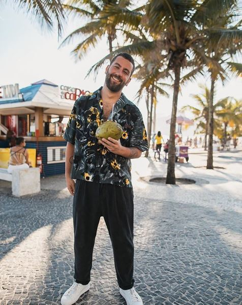 matthewzorpas: bearded man wearing a tropical shirt and holding a coconut on the beach