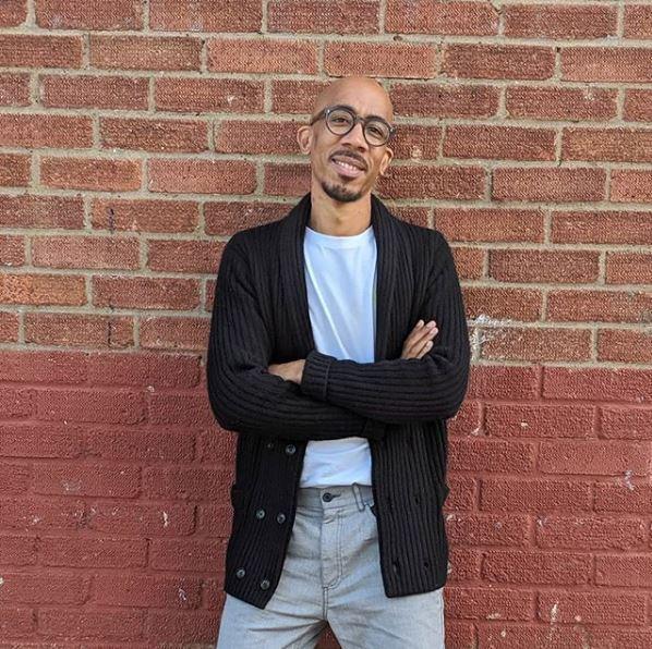 Homme noir chauve à la peau claire, avec des lunettes, appuyé contre un mur de briques