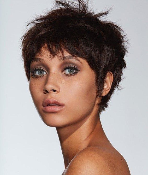 femme avec une coupe de cheveux de lutin des années 60, brun foncé et désordonné