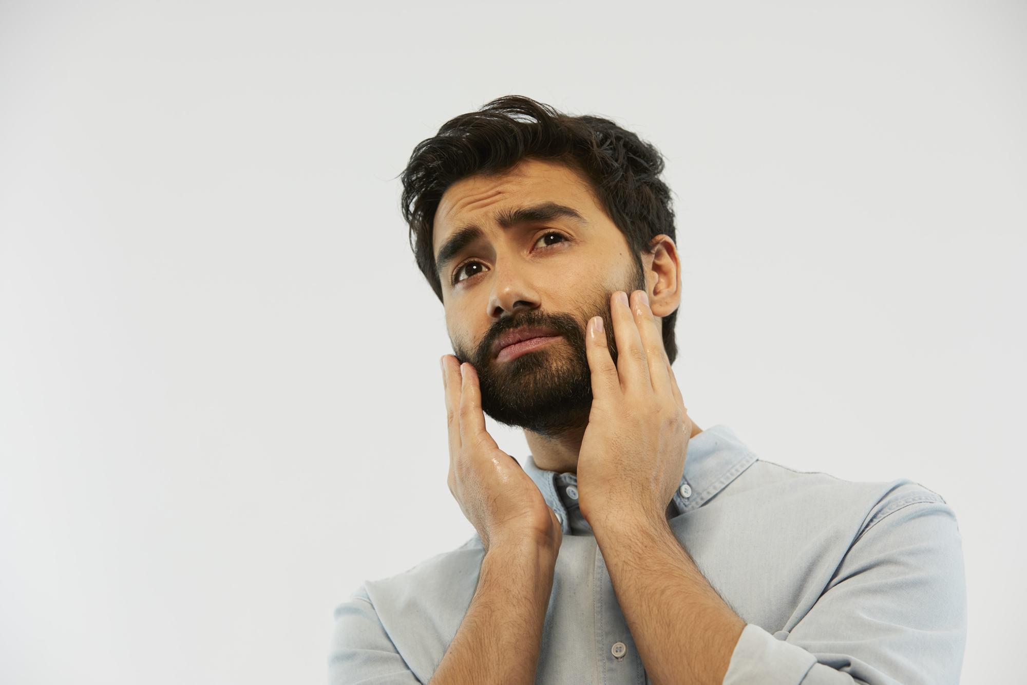 homme barbu se frottant la barbe