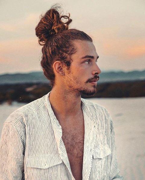 Homme aux cheveux bouclés dans un chignon d'homme