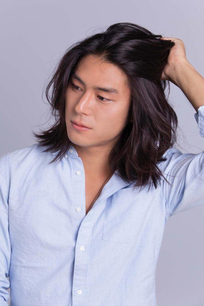 Un homme asiatique, un petit pain : Modèle masculin asiatique dont les cheveux à la longueur des épaules touchent ses cheveux