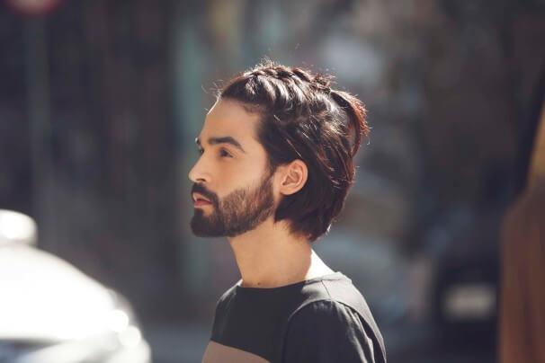 Homme aux cheveux mi-longs tressés, brun foncé et raides