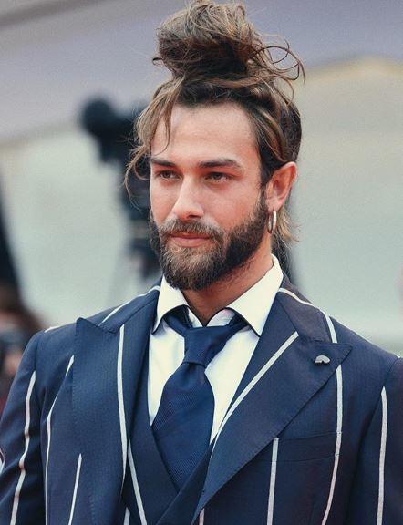 Homme aux cheveux longs bruns en chignon à nœud supérieur