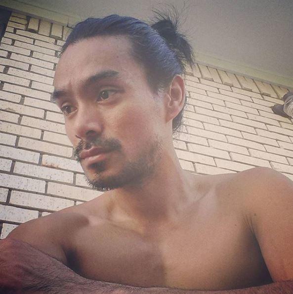 Un homme asiatique, un petit pain : Jeune homme asiatique avec un chignon d'homme haut