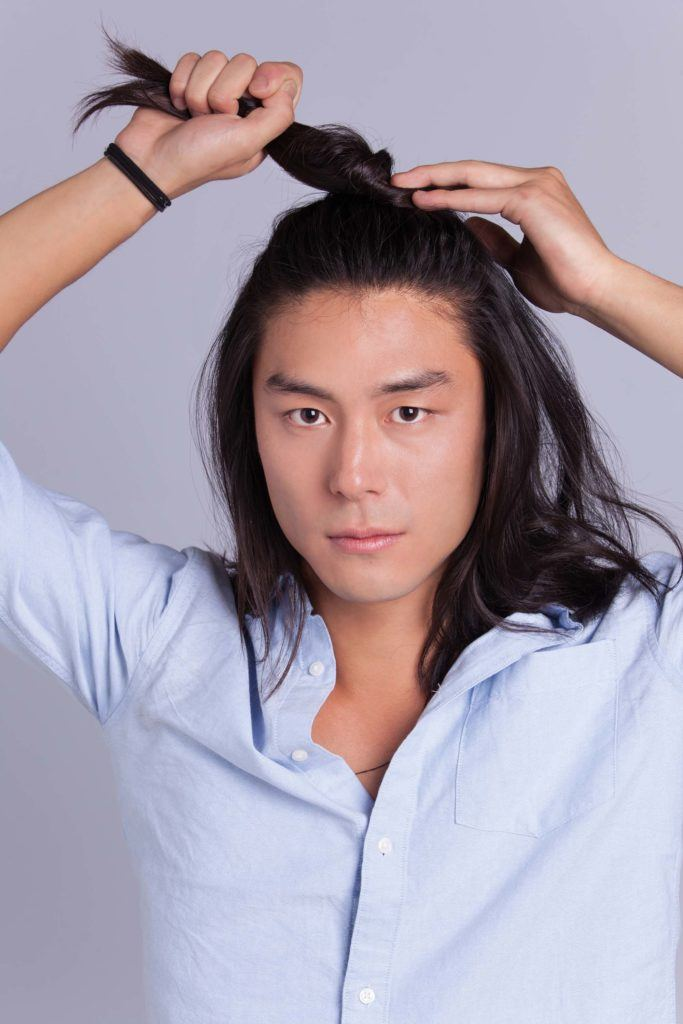 Un homme asiatique, un petit pain : Modèle masculin asiatique aux cheveux longs aux épaules, se tordant les cheveux en un chignon d'homme à moitié relevé