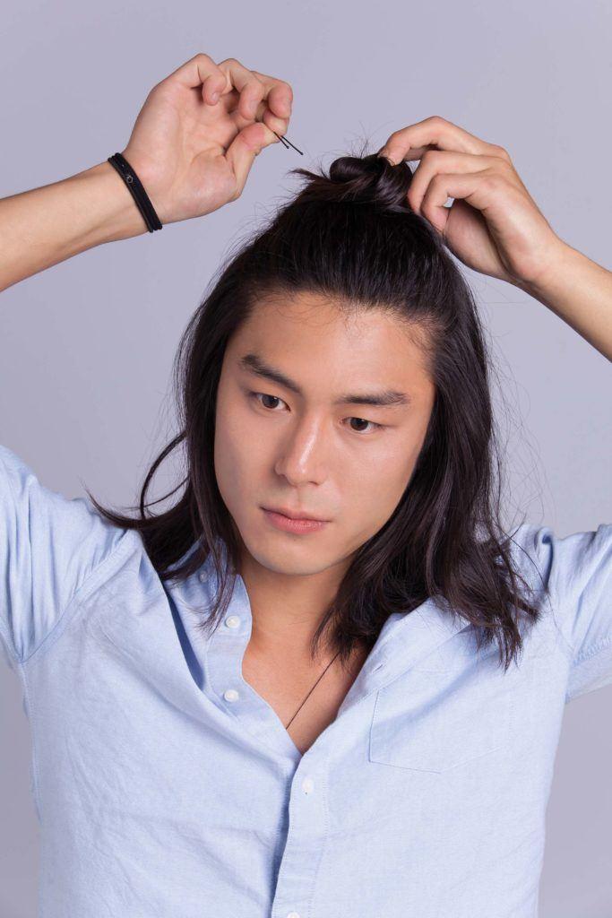 Un homme asiatique, un petit pain : Modèle masculin asiatique aux cheveux longs aux épaules, fixant un chignon d'homme à moitié relevé