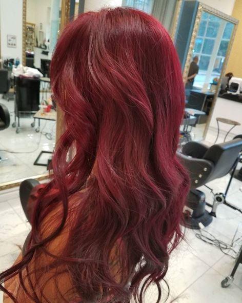 femme avec de longs cheveux ondulés d'un rouge profond