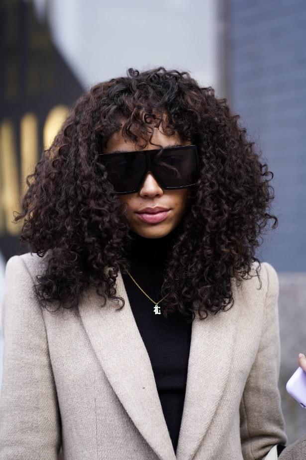 Femme aux cheveux naturels bouclés brun foncé avec une frange
