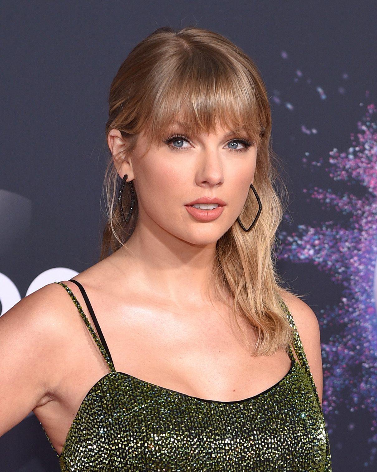 Taylor Swift avec des cheveux blonds mi-longs ondulés avec une frange complète