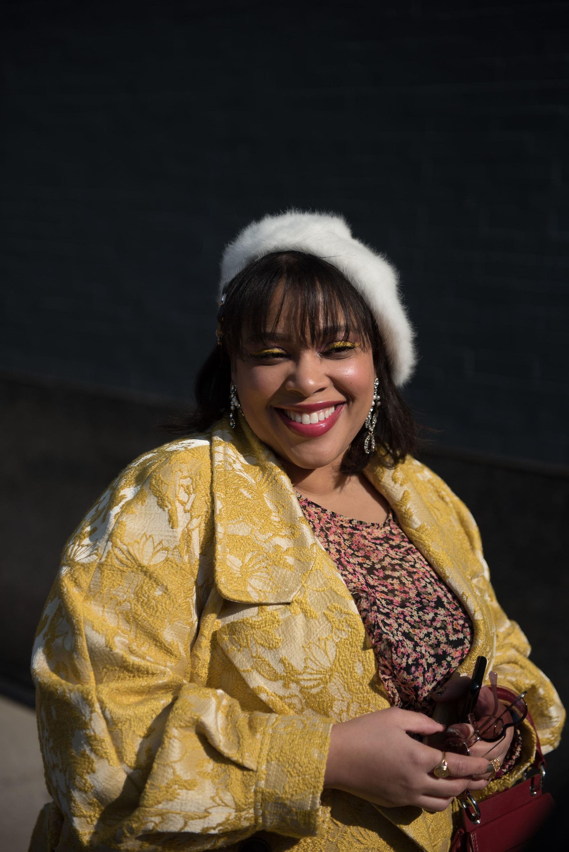 Femme souriante avec un bob marron foncé à frange, portant un béret pelucheux blanc