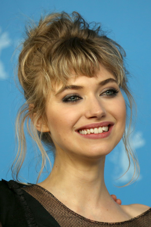 Micro-franges : Imogen Poots avec des cheveux blonds sales ondulés et des styles à micro franges dans un chignon désordonné en souriant.