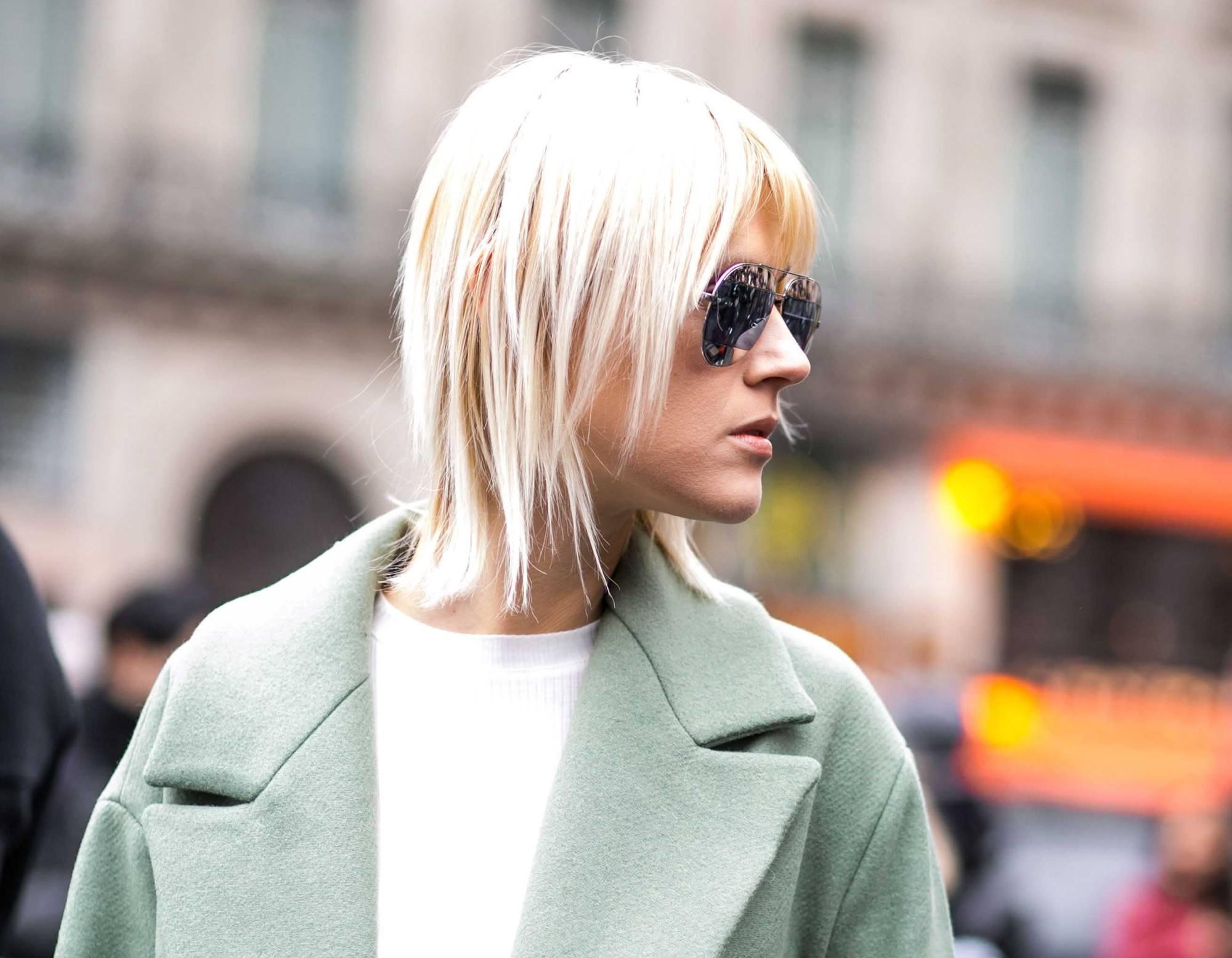 Femme blonde aux cheveux courts et à la coupe de cheveux à la frange tzigane, regardant à sa droite