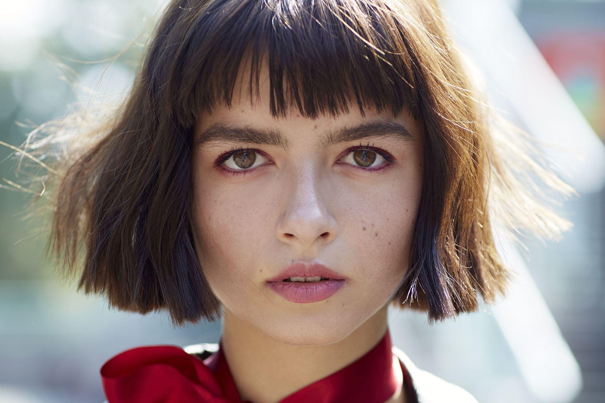 gros plan d'un mannequin de rue aux cheveux courts avec une frange, portant un foulard rouge