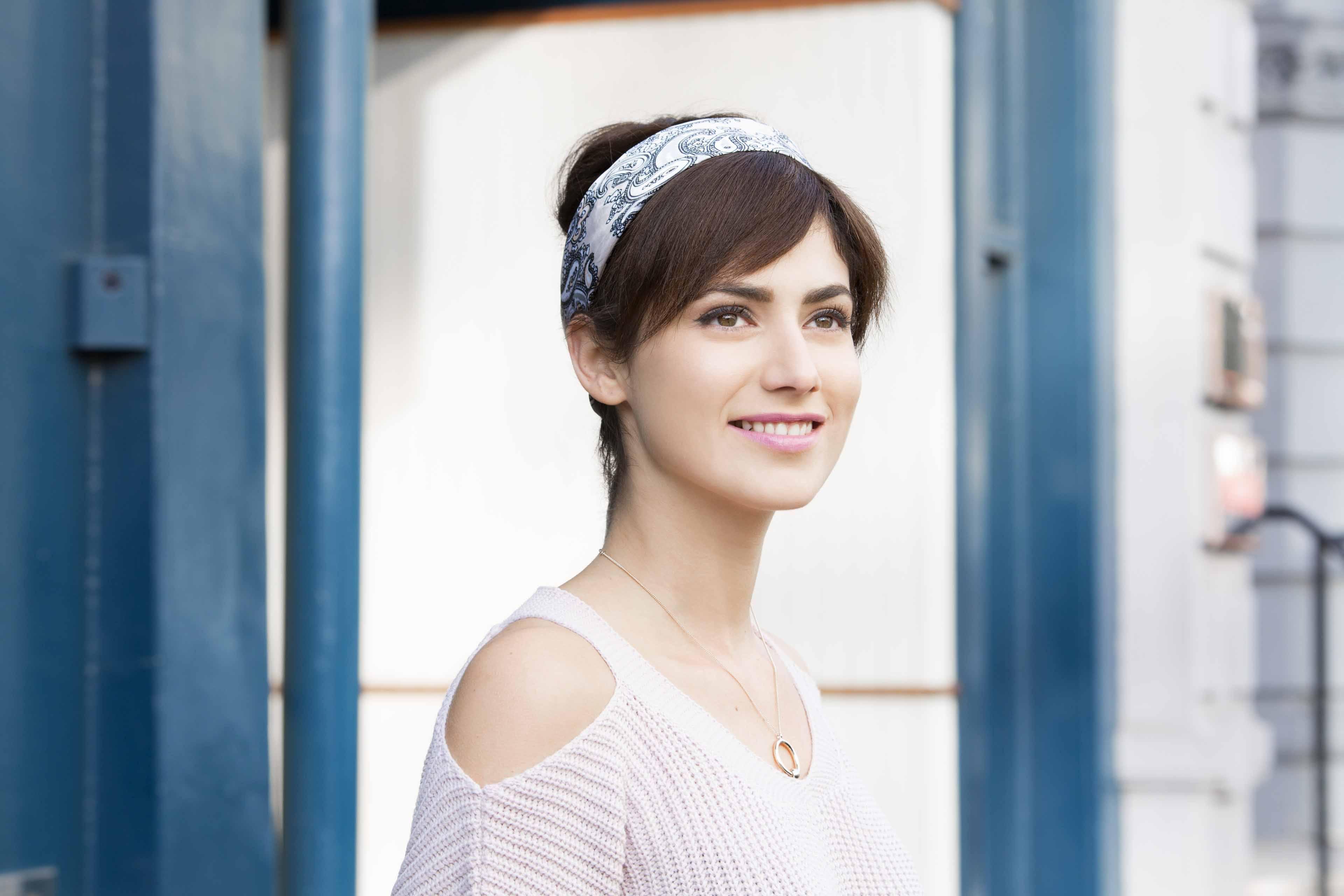 une fille avec une fausse frange de cheveux qui sourit à l'extérieur