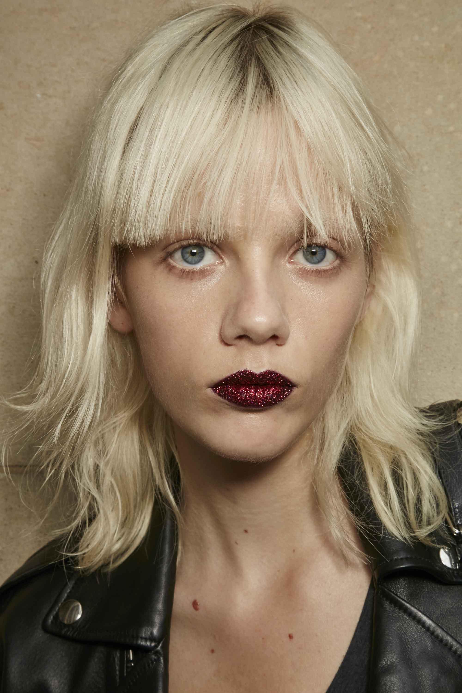 modèle aux cheveux blonds platine coupés en coupe courte et à la frange émoussée, portant du rouge à lèvres rouge foncé