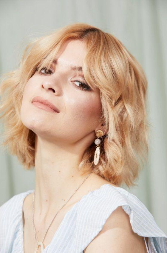 Femme avec un bob blond ondulé à la frange de rideau