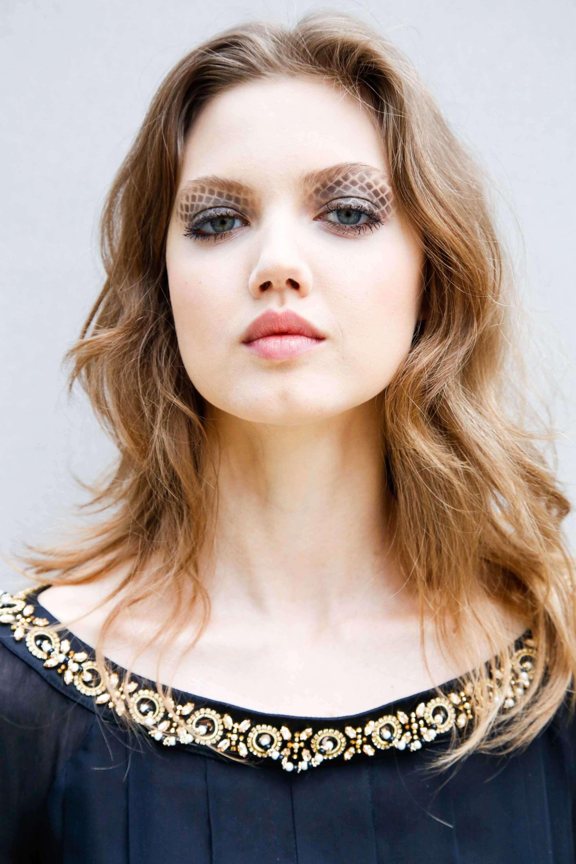 Coupes de cheveux pour cheveux épais : Gros plan d'un mannequin aux cheveux bruns clairs et ondulés, portés en coupe mi-longue et hirsute.