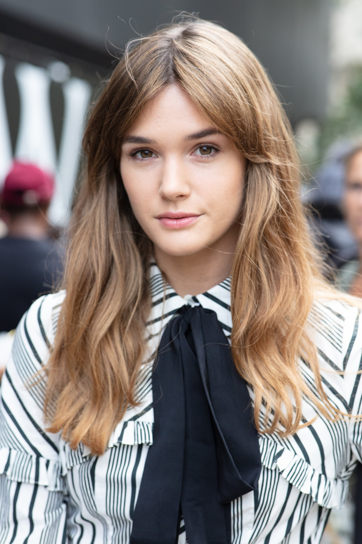 Femme brune au balayage cheveux mi-longs ondulés avec une frange de rideau