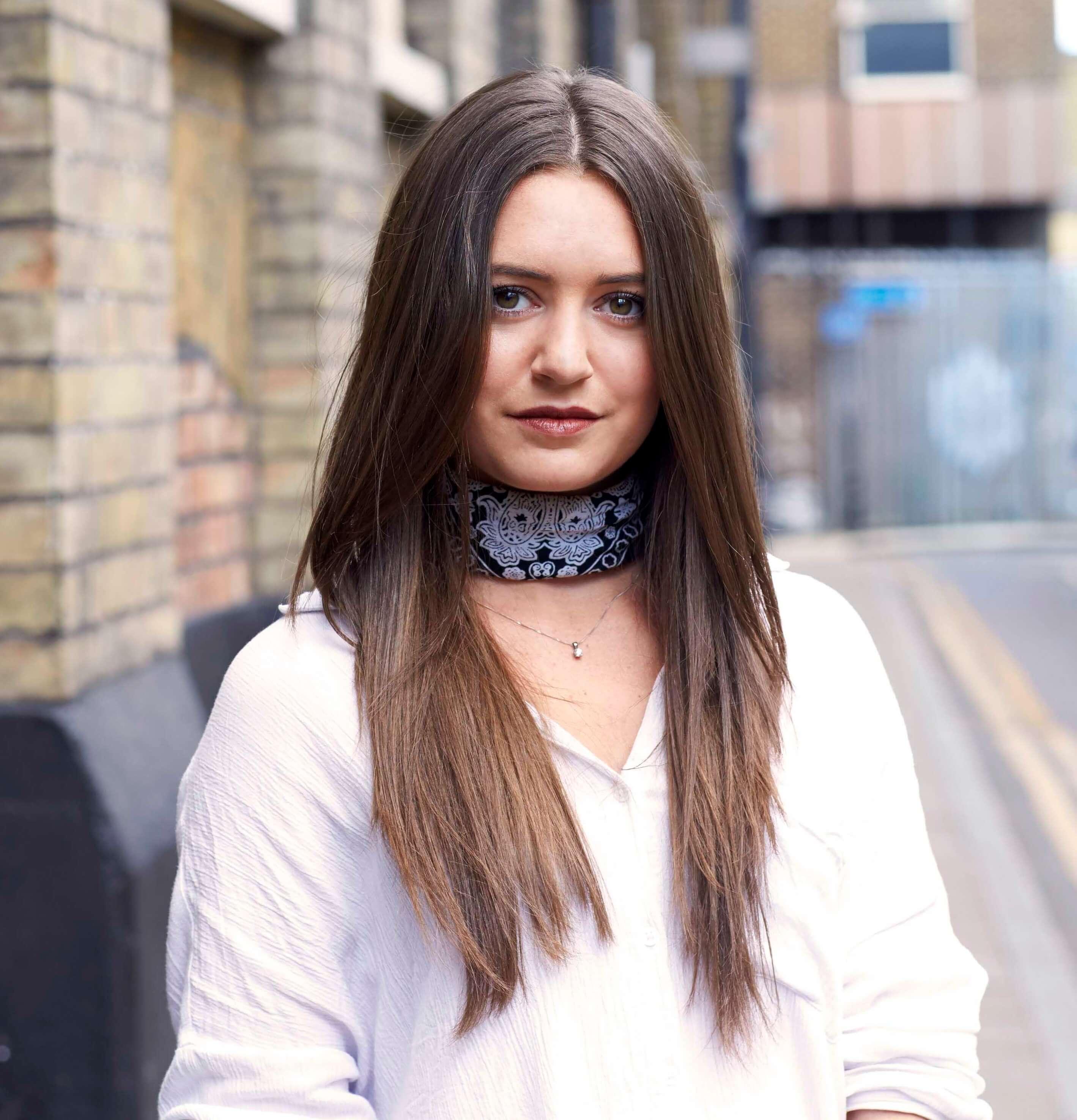 Coupes de cheveux pour cheveux épais : Plan de rue d'une femme brune aux cheveux longs avec des couches de plumes
