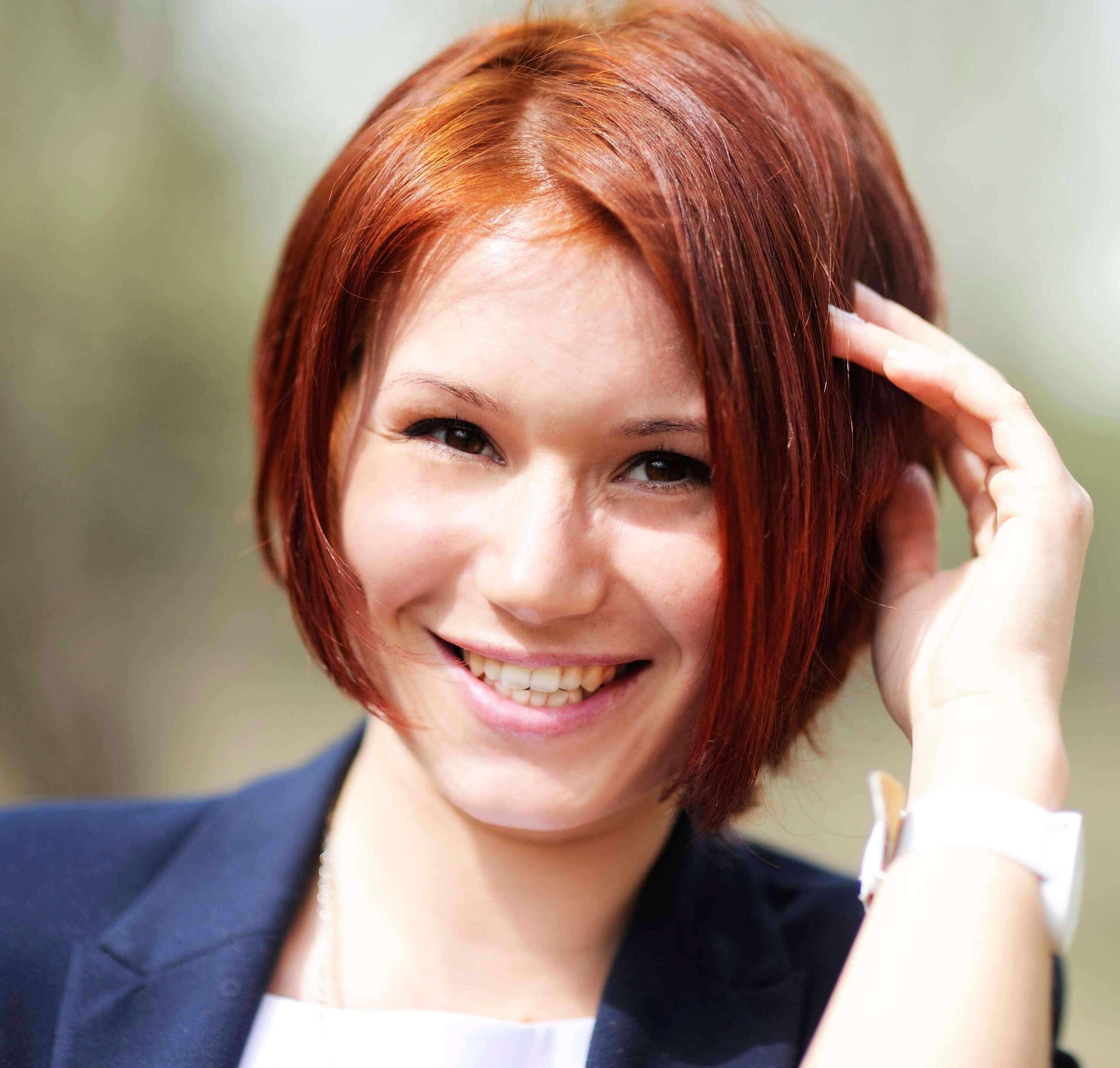 Femme aux cheveux roux avec une coupe de bobsleigh en biais, qui se touche les cheveux avec ses mains.