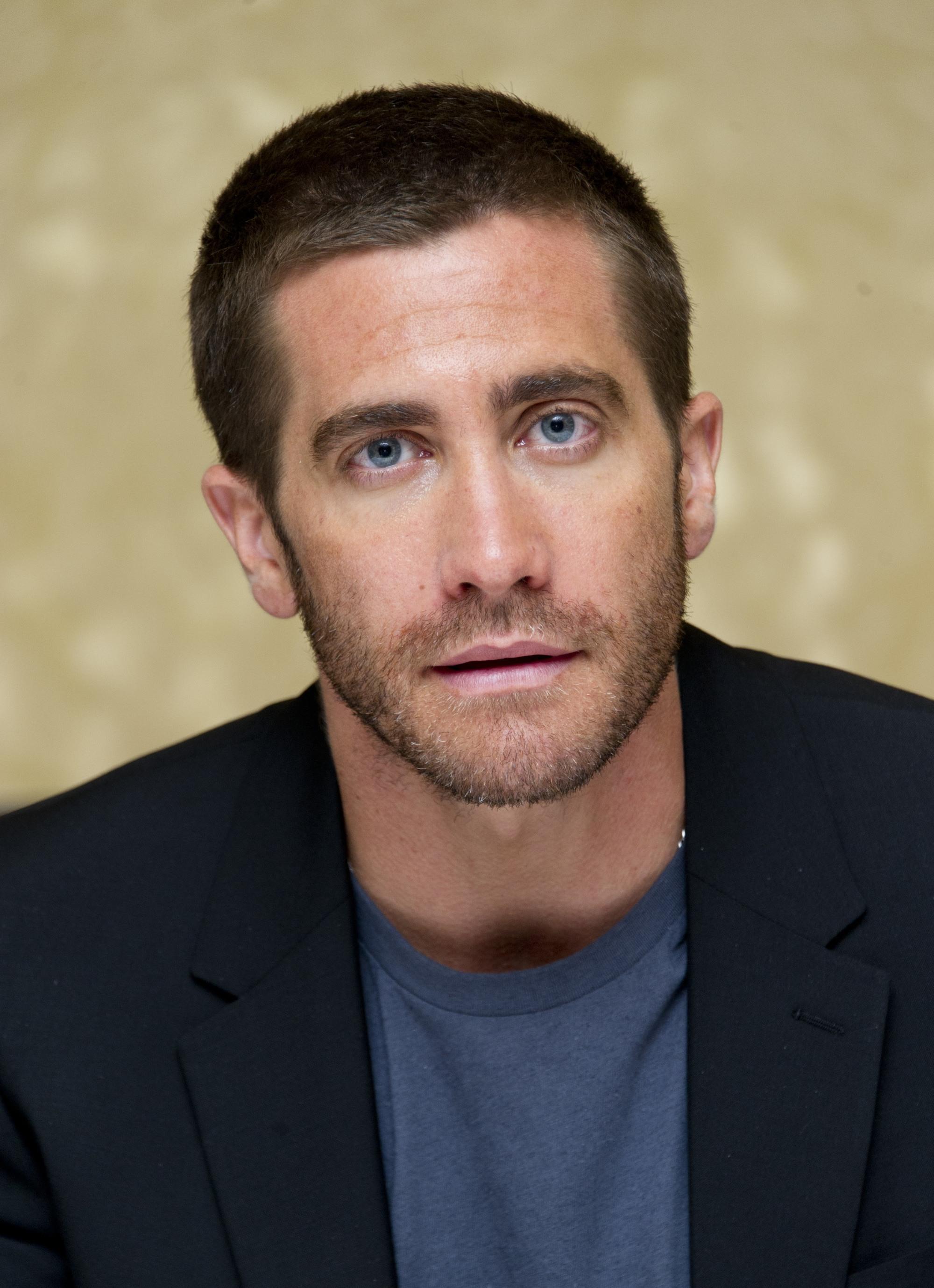 Coiffures pour le recul de la ligne des cheveux : Photographie de Jake Gyllenhaal avec une coupe de cheveux en raie, portant un t-shirt bleu et un blazer noir