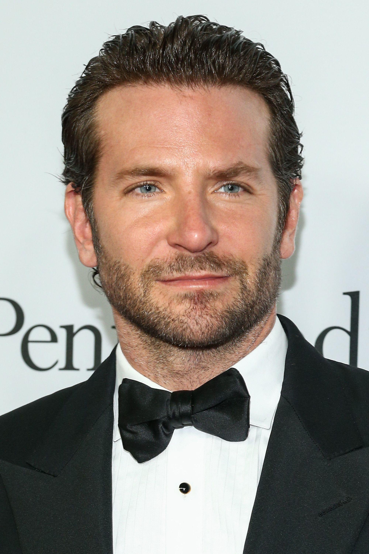 Coiffures pour le recul de la ligne des cheveux : Photographie de Bradley Cooper avec des cheveux foncés en arrière peignés, portant un smoking et un nœud papillon noir
