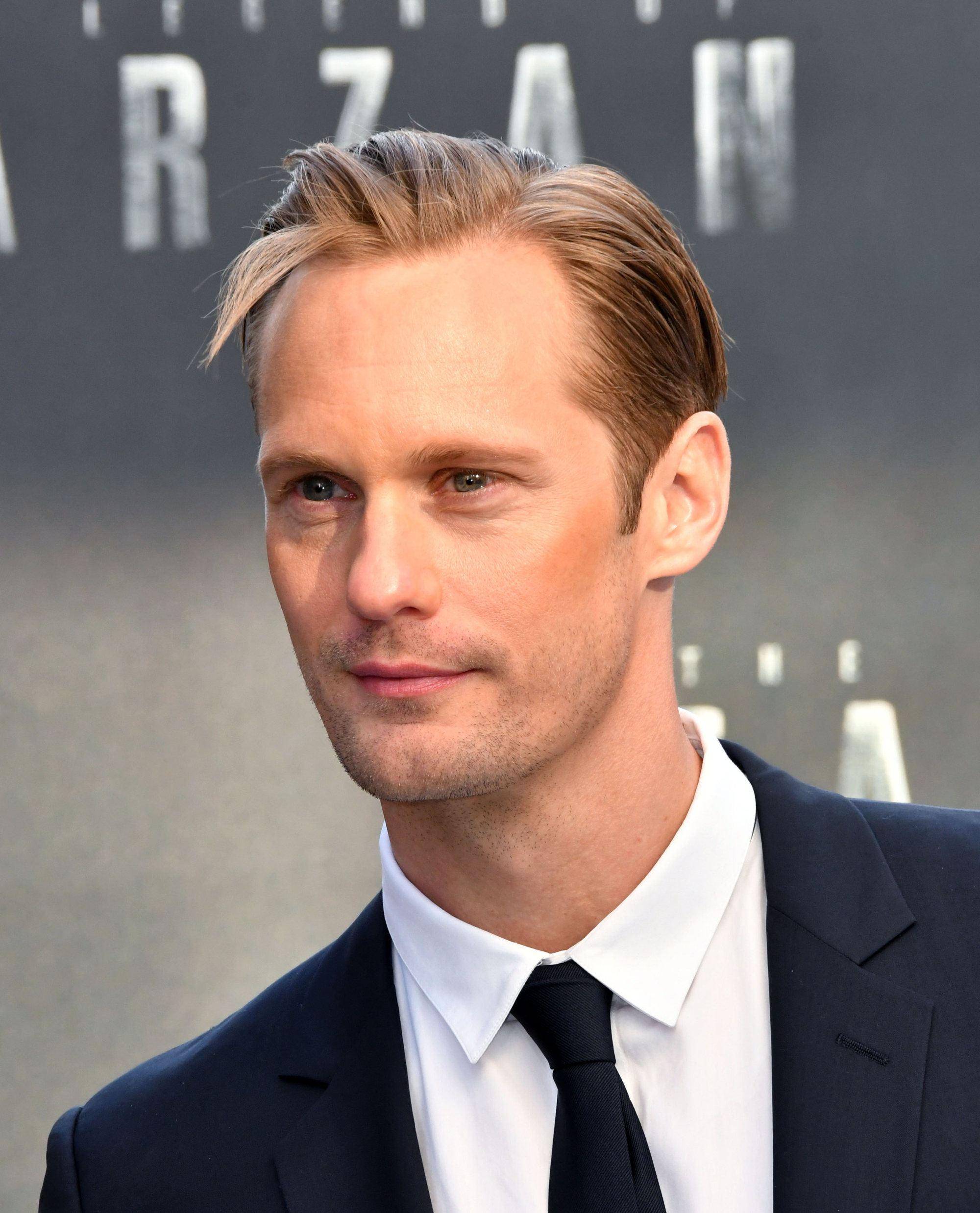 Coiffures pour le recul de la ligne des cheveux : Gros plan d'Alexander Skarsgard avec des cheveux blonds dans une coiffure au peigne fin avec séparation latérale