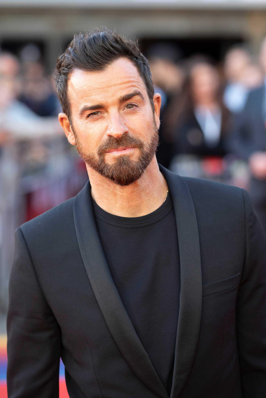 Coiffures pour le recul de la ligne des cheveux : Justin Theroux, cheveux châtain foncé, coiffé en touffe avec une pointe de veuve, portant un t-shirt noir et un blazer