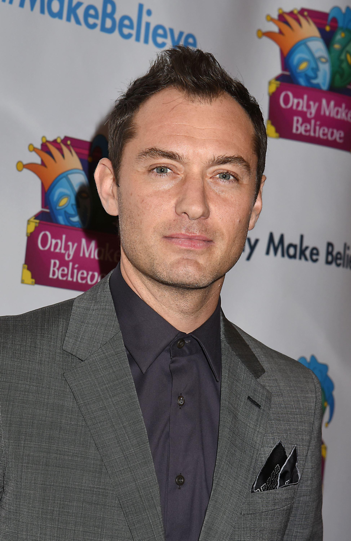 Coiffures pour le recul de la ligne des cheveux : Jude Law avec des cheveux bruns dans un style mohawk, portant un costume gris
