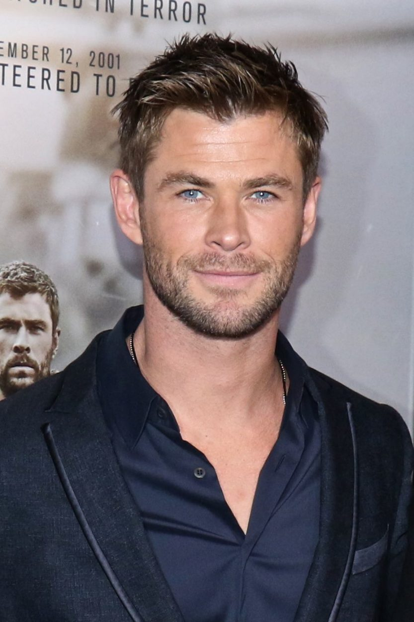 Hairstyles for receding hairline: Headshot of Chris Hemsworth with spiky crew cut hair, wearing a navy suit