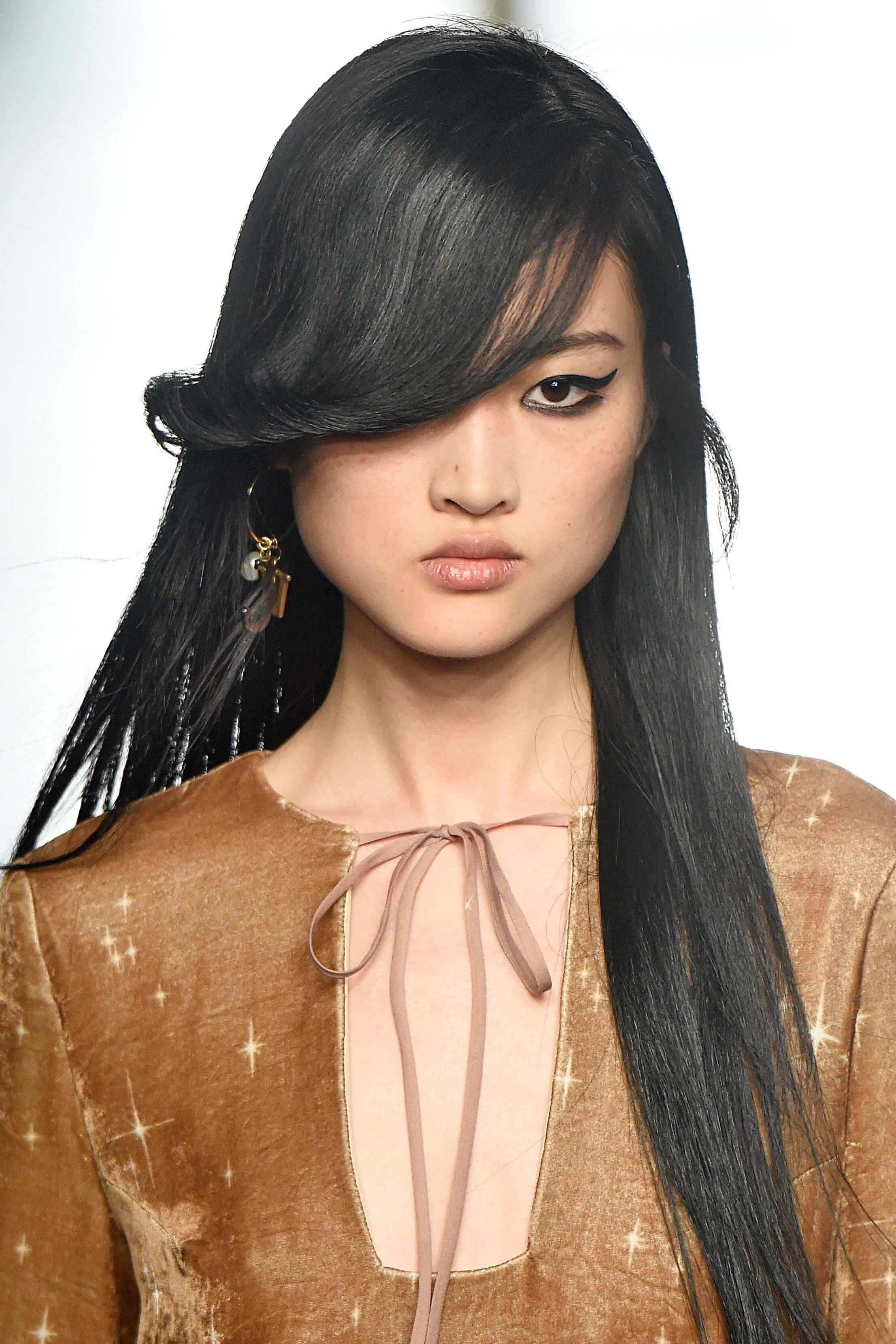 Femme asiatique aux cheveux longs et à la frange balayée sur le côté : coiffures pour visages ronds